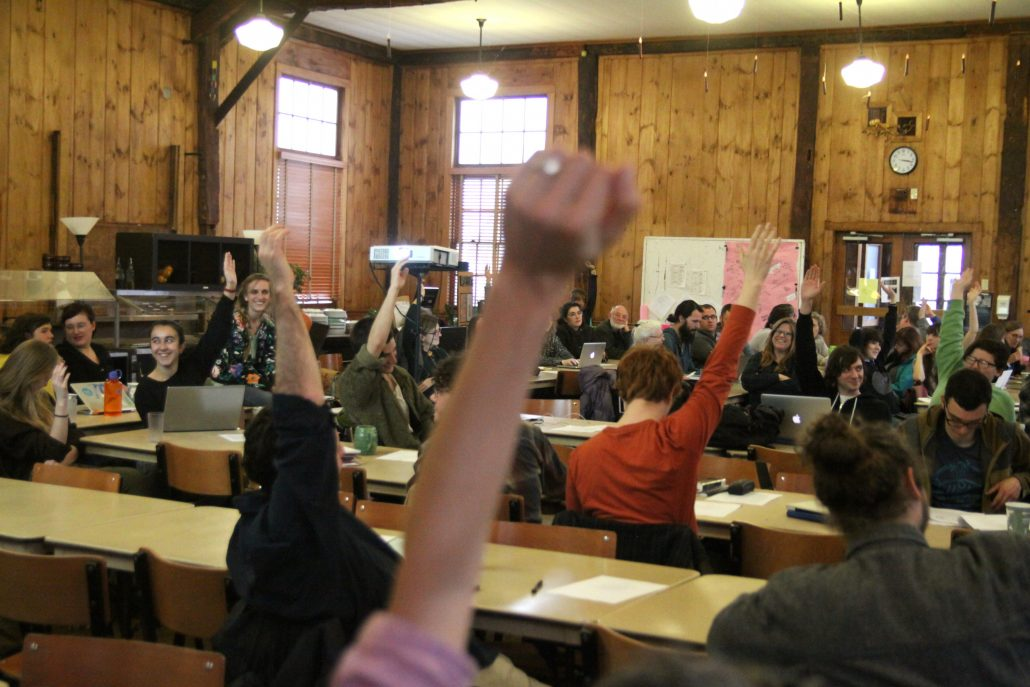 hands being raised by people during town meeting