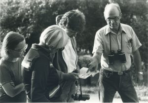 John MacArthur wearing a pair of binoculars while pointing to a piece of paper in child's hand and gazing at the camera.