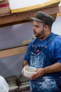 Roberto Lugo holding a ceramic bowl