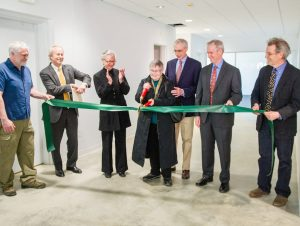 (pictured right, at center, joined by Dan Cotter, director of plant and operations, former chair Dean Nicyper '76, former president Ellen McCulloch-Lovell, President Kevin Quigley, and visual arts faculty member Tim Segar) all are clapping while one cuts a green ribbon