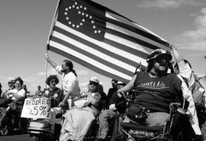 black and white image of people holding up the American flag with a wheelchair symbol