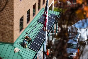 Workers installing brand new solar panels on a green roof