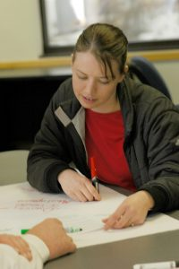 student writing on poster paper