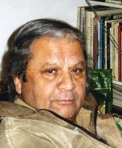 Image of Jaysinh Birjepatil sitting in front of books