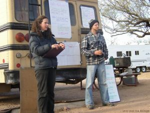 Two people presenting outside next to a bus