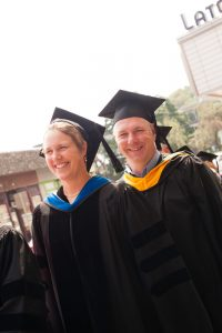Two people wearing graduation cap and gown