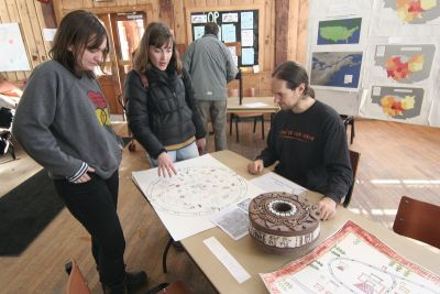 professor looks at cartography projects with students.