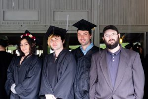 four students posing wearing their graduation caps and gowns
