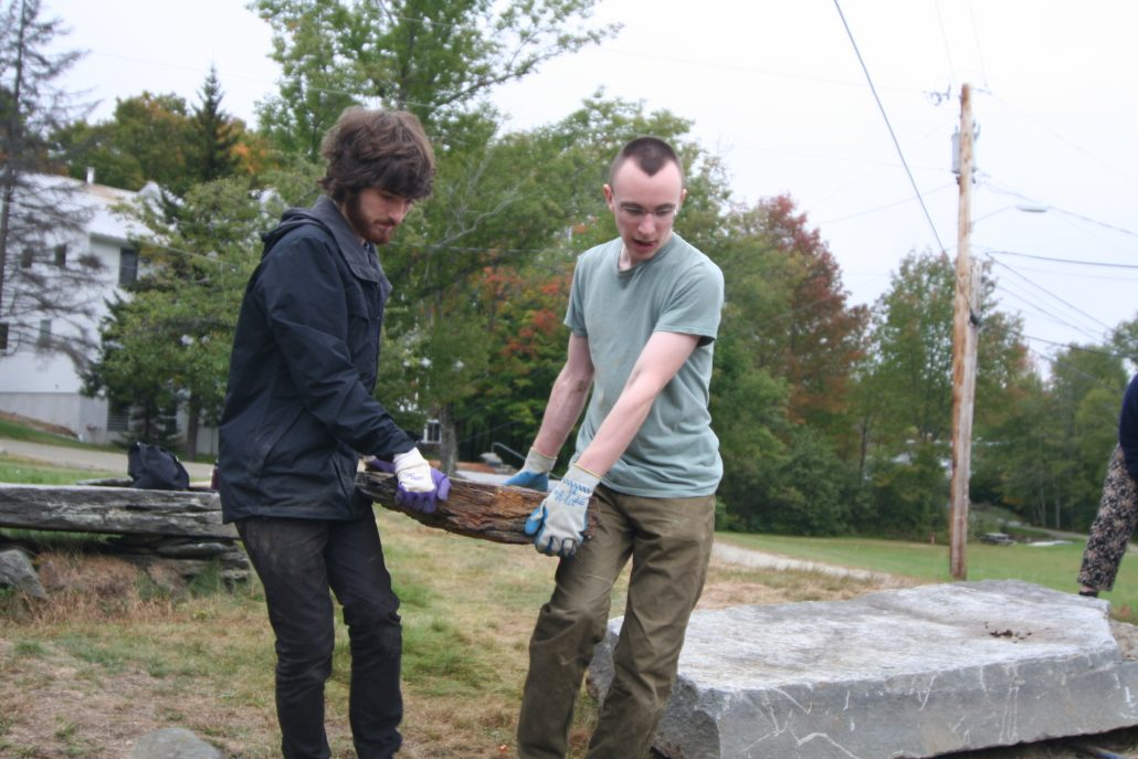 two students carrying a slab of rock