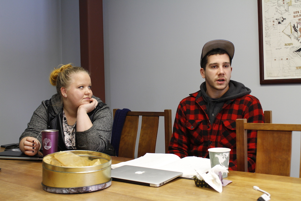 two students speaking at a table