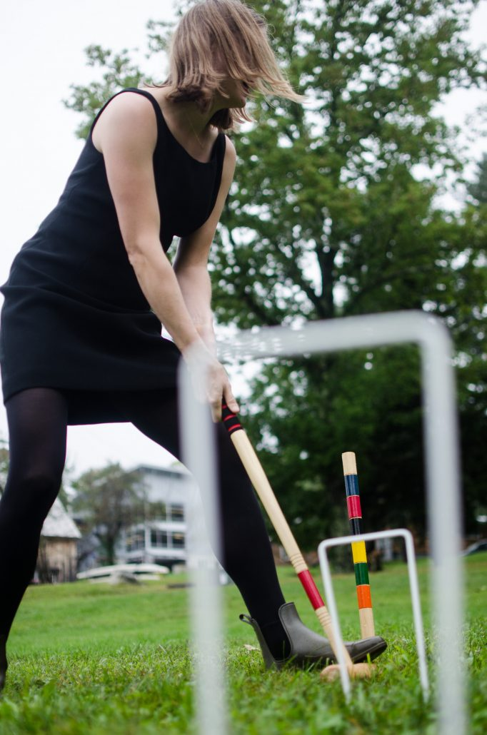 A student laughing while playing croquet