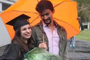 A graduate and a well-wisher under an umbrella