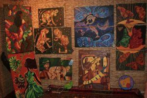 Paintings of nude brown women, bright colors, and animals