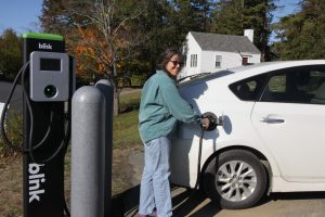 Jenny Ramstetter charging up a car at a EV charging station