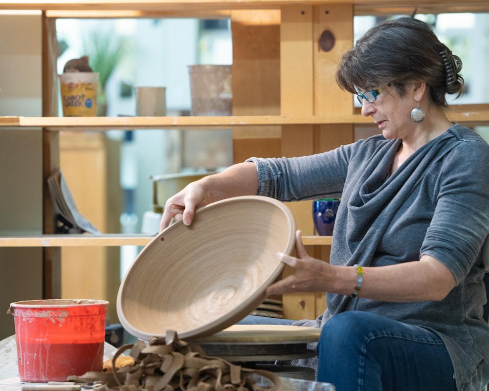 Teta holding an unglazed bowl