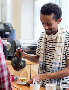 Dagmawi Iyasu pouring a cup a coffee