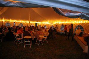 Marlboro Alumni seated under a tent at night