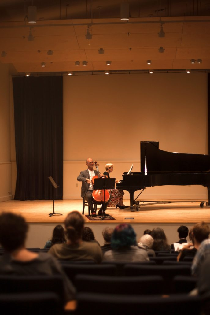 Two musicians playing the cello and piano on a grand stage