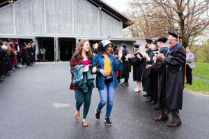 Prospective graduates walk down hill flanked by faculty